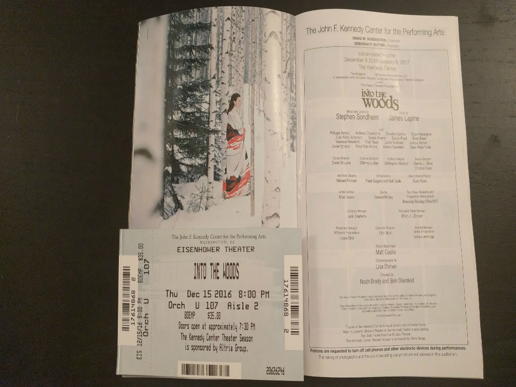 """A playbill opened to the feature page of Sondheim's """"Into the Woods."""" On the left, a drawing of a woman facing to the right wrapped in a red, white, and black blanket. There's a pine tree on the left and birch trees around here, as well as snow. On the right are all the credits for the Kennedy Center and the Fiasco Theater Production of """"Into the Woods""""."""