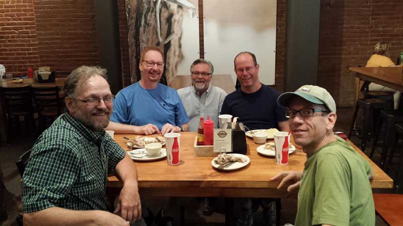 Founder, Scott Moore, sits between violinists Carl Johnston and Cal Lewis. Principal bassoonist and principal horn, Eric Anderson and Gordon James sit on the opposite side